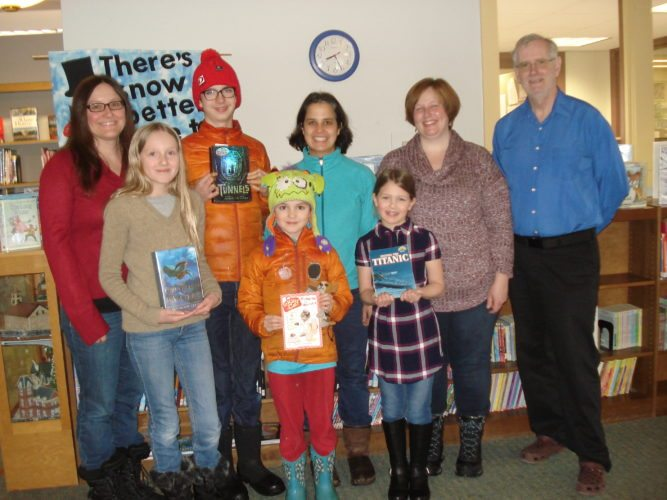 Local Home School parents and children who participated in the November Reading Challenge are shown holding a favorite book at the Saranac Lake Free Library. Back row Samantha Marocco, Galen Halasz (seventh grade), Sunita Halasz, Allison Rozon, and Library Director Peter Benson. Front row Olivia Marocco (sixth grade), Oliver Halasz (third grade) and Rachael Rozon (third grade). Jenna Stainken (fifth grade) also participated in the Challenge. (Photo provided — Pat Wiley)