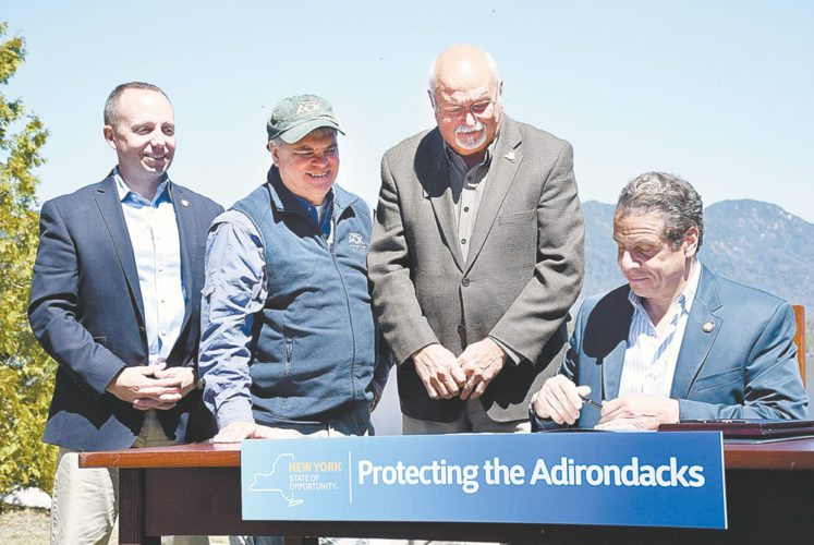 From left, state Department of Environmental Conservation Commissioner Basil Seggos, Adirondack Mountain Club Executive Director Neil Woodworth and town of North Hudson Supervisor Ron Moore stand by as Gov. Andrew Cuomo signs off on the state's purchase of the Boreas Ponds land tract in May 2016 at Elk Lake in the Adirondacks. (Enterprise photo — Justin A. Levine)