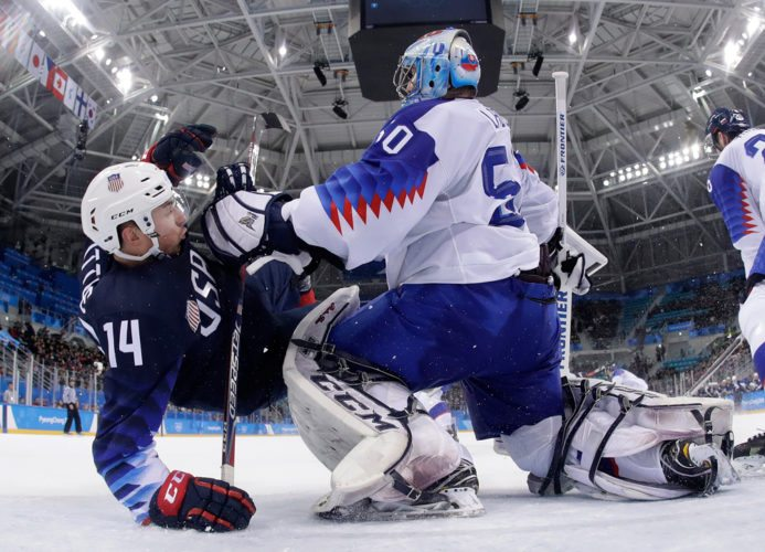 Slovakia goalie Jan Laco pushes Broc Little, of the United States, down during the third period of Tuesday's qualification round game in Gangneung, South Korea. (AP photo — Julio Cortez, Pool)