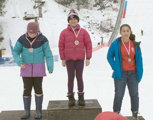 Lake Placid native Kai McKinnon stands atop the podium after taking first place in the ladies 20- and 30-meter ski jumping competitions Feb. 10-11 in Salisbury, Connecticut. (Provided photo)