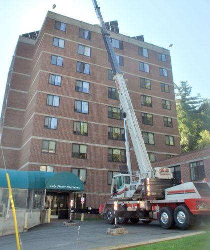 A crane is used to upgrade an elevator at Lake Flower Apartments in Saranac Lake in 2016. (Enterprise photo — Chris Knight)