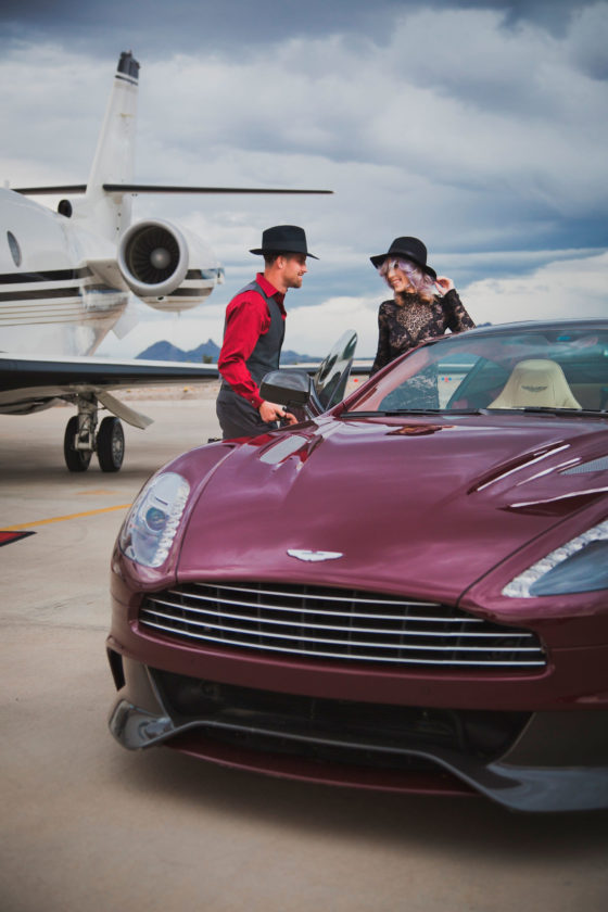 PHOTO SUBMITTED A promotional image for Watson's Hat Shop shows two models wearing Eric Waton's custom-made hats on a set with a private jet and an Aston Martin car that belong to two of Watson's customers.