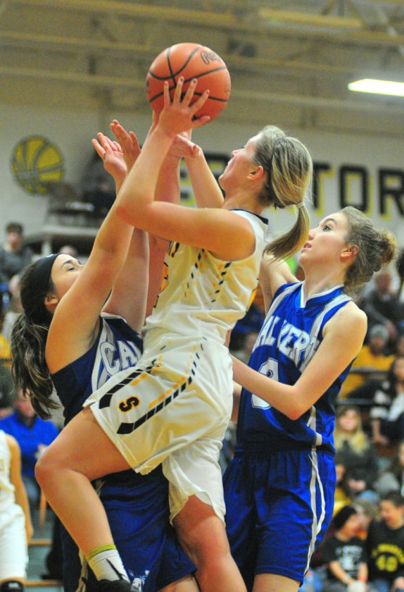 PHOTO BY PAT GAIETTO St.  Wendelin's Hailee Burns shoots between Calvert's Claire Thompson (left) and Madison Jones.