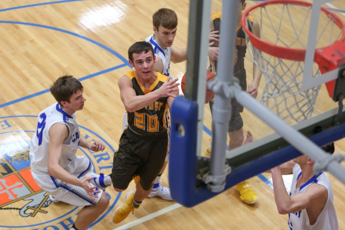PHOTOBYSTEVEWILLIAMS Old Fort's Jacob Webb sets his eyes on the basket after he splits Calvert defenders on his way down the lane for the score Saturday in Tiffin.