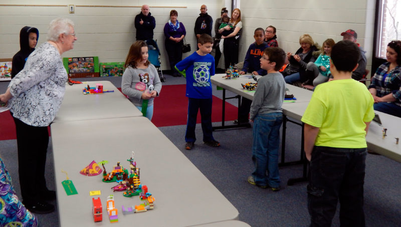 PHOTO BY SETH WEBER David Wyatt (center), 10, tells Junior Library Manager Connie Cole about his island scene during the Lego contest at Tiffin-Seneca Public Library.