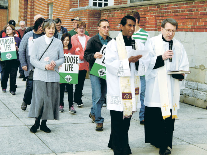 PHOTO BY MARYANN KROMER Father Kishore Kottana (front, left) and Father Joseph Szybka lead a March for Life Sunday from St. Joseph Church to St. Joseph Cemetery. About 70 people participated.