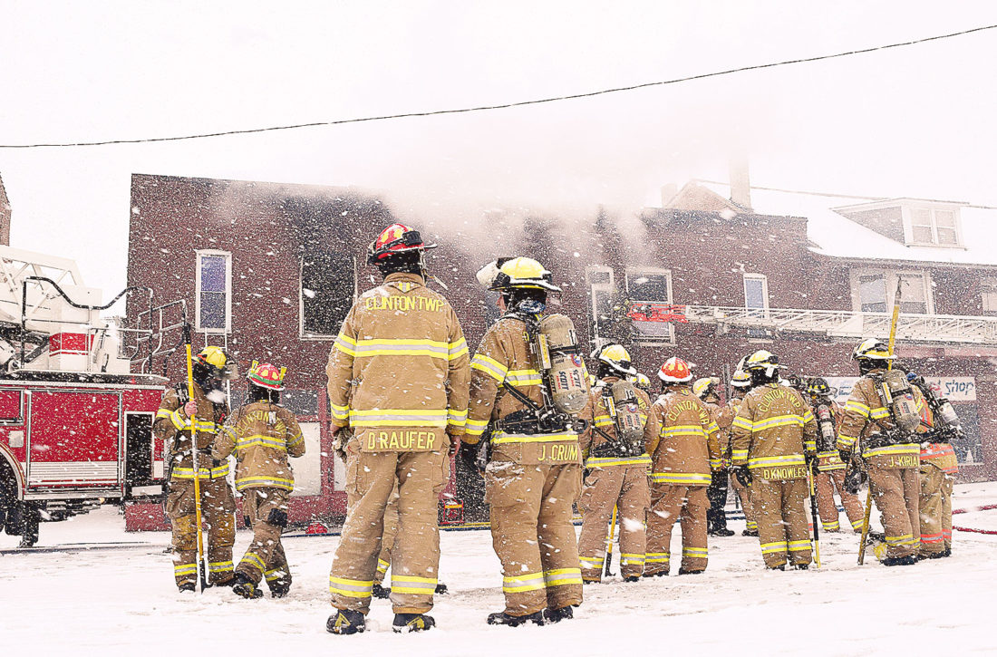 PHOTO BY JILL GOSCHE Firefighters work at the scene of the East Market Street fire Friday afternoon.