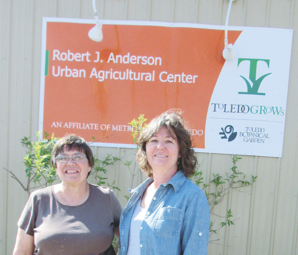 Sister Rita and New Riegel native Yvonne (Steyer) Dubielak, outreach and education coordinator for Toledo GROWs, pose in front of the sign on the front of the building in downtown Toledo.