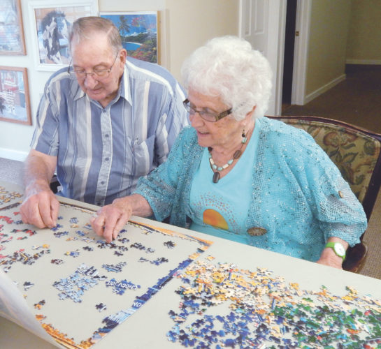 PHOTO BY NICOLE WALBY Gene Fatzinger and Joann Hatton work on their latest puzzle together at Seneca House.