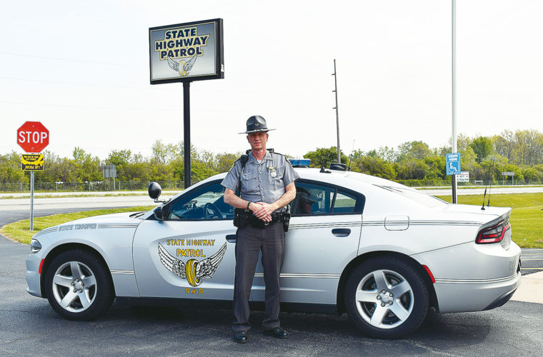 PHOTO BY JILL GOSCHE Trooper Jim Van Camp stands near his cruiser at the Fremont post of State Highway Patrol Friday morning. To view more photos from this event, visit cu.advertiser-tribune.com.
