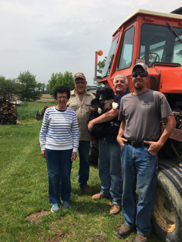 PHOTO SUBMITTED Shirley Schreiner (from left), Allan Schreiner, Mark Schreiner and Mike Schreiner take a break from farming to take a pose next to a tractor Saturday afternoon. The Schreiner family owns a farm in Republic.