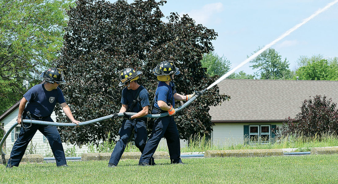 PHOTO BY JILL GOSCHE Bill Hoffert (from left), Drew Lucius and Keith Johnson, firefighter-medics for Tiffin Fire Rescue Division, spray water during an exercise behind Tiffin Mall Monday afternoon. To view more photos from this event, visit cu.advertiser-tribune.com.