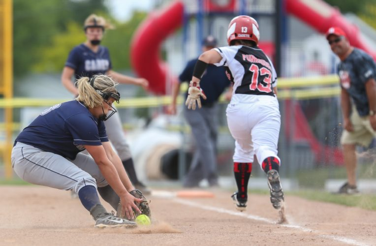 PHOTO BY STEVE WILLIAMS Carey pitcher Dani Berardinelli-Clark hustles out of the circle to chase down a bunt hit as Hilltop's Audrey Funkhouser races towards first base in an attempt to beat the throw.