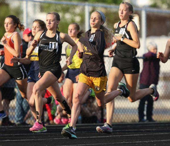 PHOTO BY STEVE WILLIAMS Sophia Volpe (second from right) leads the pack around the first turn of the 3,200, and goes on the win from start to finish at regionals in Tiffin Friday.