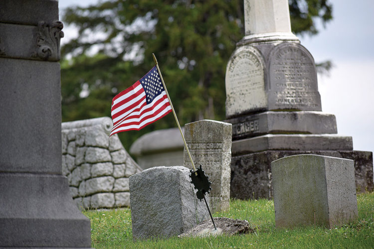 PHOTO BY JILL GOSCHE A flag adorns a veteran's grave at Greenlawn Cemetery Saturday afternoon.