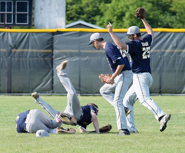 PHOTO BY JILL GOSCHE New Riegel's Brian Hughes (third from left) and Michael Kirian (far right) celebrate Shane Halcomb's catch for an out as Cole Noftz dives over him during the regional final game against Dalton in Lorain Saturday.