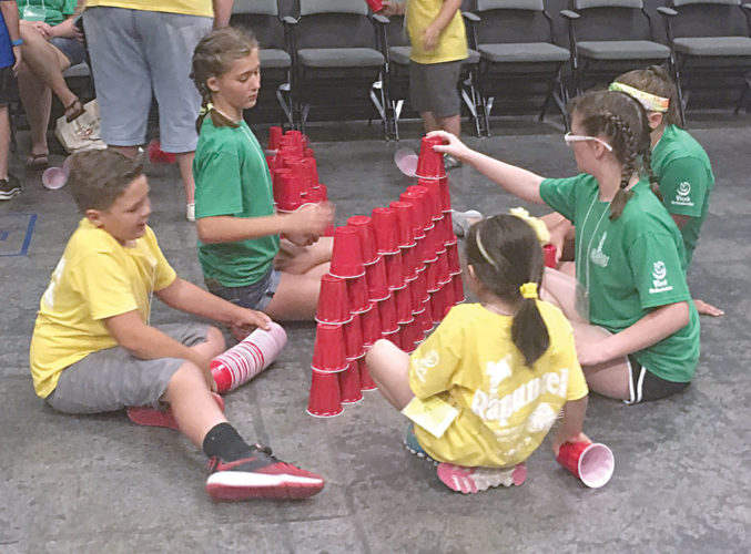 PHOTO BY NICOLE WALBY Campers erect a tower of plastic cups in a team during a workshop Tuesday during The Ritz Summer Theater Camp.