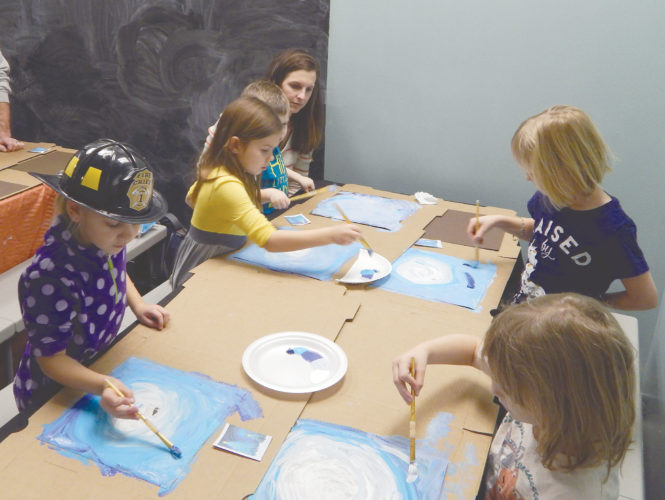 PHOTO BY MARYANN KROMER Children create a winter scene during a Saturday painting class at the Children's Museum.