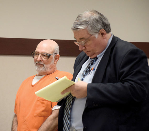 PHOTO BY JILL GOSCHE Timothy W. Woodland (left) stands next to his attorney, Howard Elliot, for sentencing during a hearing in Seneca County Common Pleas Court Judge Steve Shuff's courtroom Monday morning.