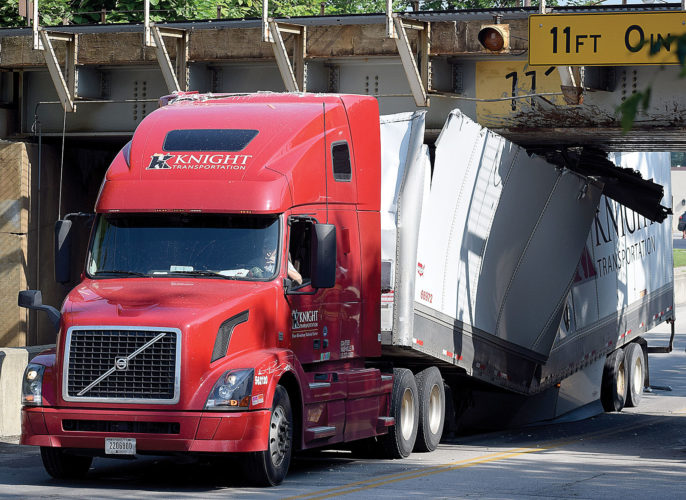 PHOTO BY JILL GOSCHE A semi trailer broke in half when the truck and trailer struck the North Washington Street viaduct Monday morning.
