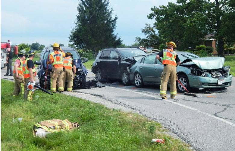 PHOTO BY JACOB GURNEY Rescue personnel clean up debris following a multiple-vehicle accident at US 224 and CR 19 Thursday afternoon.
