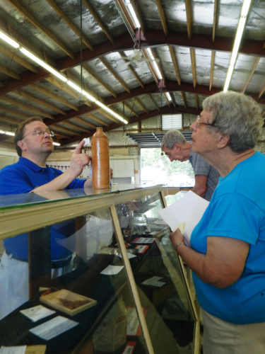 PHOTO BY NICOLE WALBY Gene Chintala (left), member of the Seneca County Fair Board, and Bob Berg (center) and Dorothy Berg, award a first-place ribbon to a china pottery entry during Crafts and Collections judging Monday.