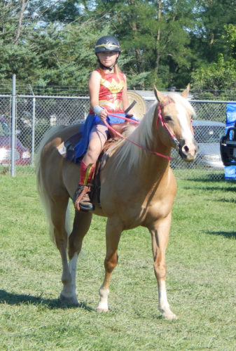 PHOTO BY JIMMY FLINT Savannah Ley prepares for the horse costume competition at the Seneca County Fair Tuesday evening. Ley dressed as Wonder Woman and rode her horse, Skippy.