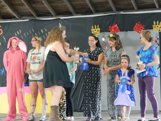 PHOTO BY JIMMY FLINT Abby Lucius (center) receives a blue ribbon during the Style Revue Tuesday as Jenna Elchert (right), who modeled Lucius' black-and-white romper, looks on. Lucius won first place in the Sew for Others category for participants 13 or older and is to move on to the Ohio State Fair.