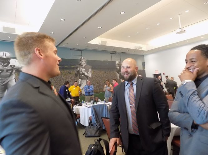 PHOTO BY ZACH BAKER Heidelberg defensive lineman Austin Crow (left) shares a laugh with coach Scott Donaldson (center) and wide receiver Demetrius Magee during the Ohio Athletic Conference's football media day at the Pro Football Hall of Fame in Canton Thursday.