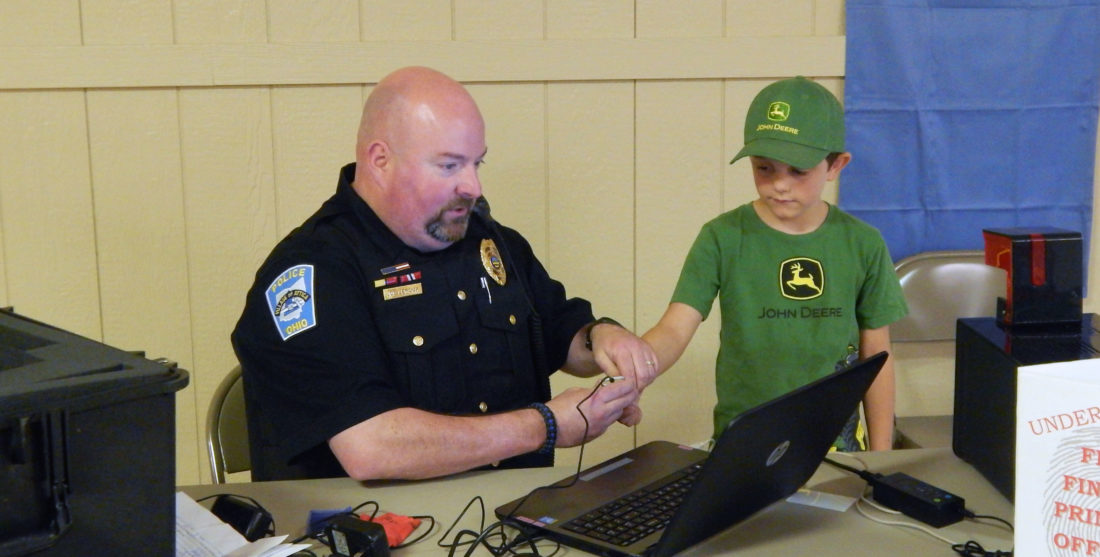 PHOTO BY JACOB GURNEY Captain Joe Leroux (left) of Attica Police Department helps Colton McConnell, of Attica, take his fingerprint during the Attica Independent Fair Saturday afternoon.