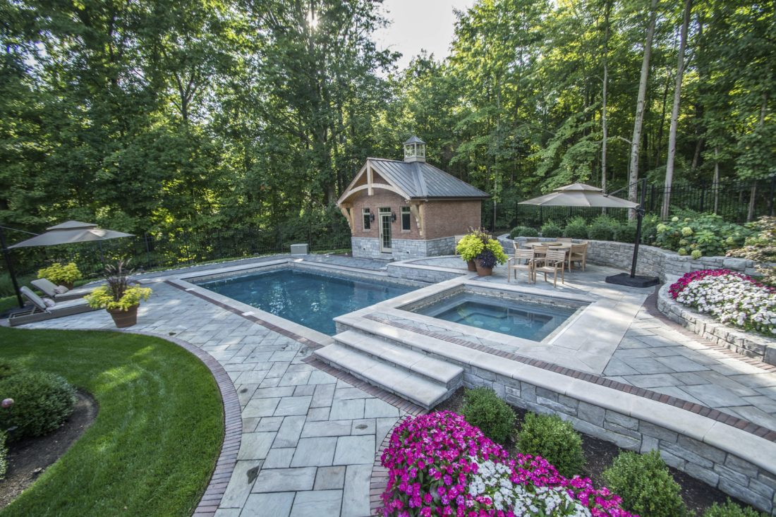 This 2017 photo provided by Grunder Landscaping shows a contrasting mix of  long-flowering plants separated from the pool water by a walkway in Dayton,  Ohio. - Swimming-pool Landscaping News, Sports, Jobs - Altoona Mirror