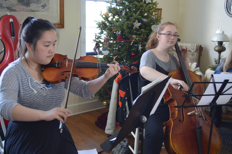 "Haley Gustafson | Daily Press Key Club students Suki Zhao, front, and Janel LaPalm perform ""Angels we have Heard on High"" during the annual Christmas open house at the Sand Point Lighthouse in Escanaba in 2016. An open house was also  held at the Delta County Historical Museum."