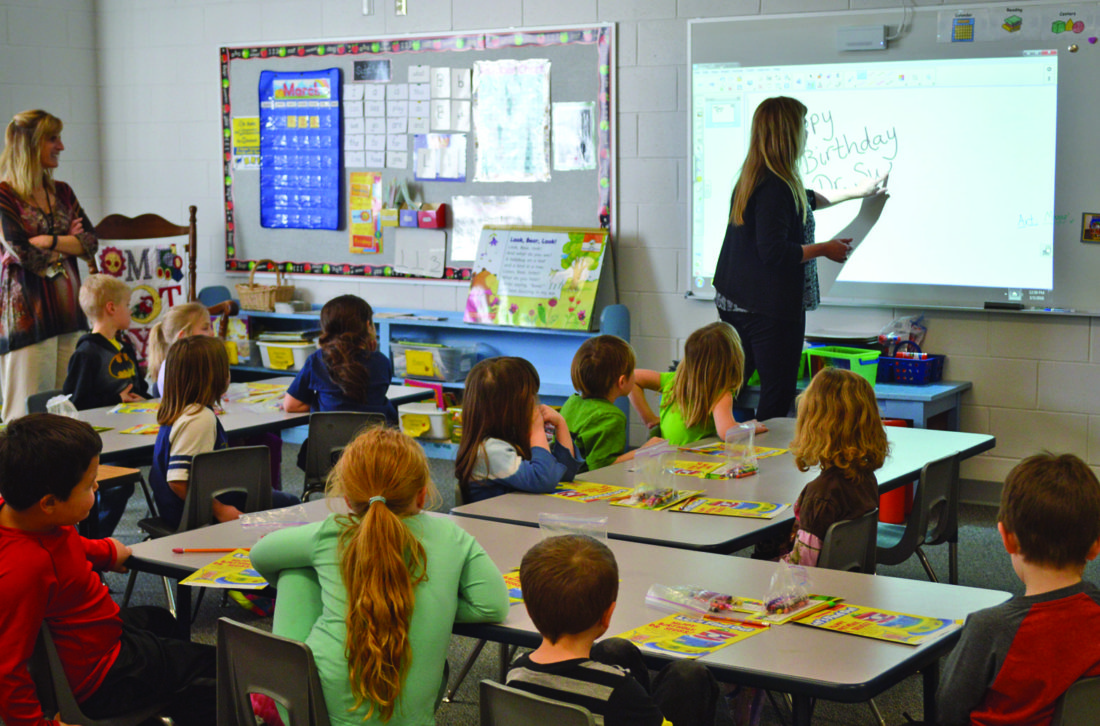 Ilsa Matthes   Daily Press Students in Connie Wells' kindergarten class watch as she uses the SMART Board in her new classroom to write ÒHappy Birthday Dr. Seuss!Ó The board allows Wells and her students to write and draw using only their fingertips.