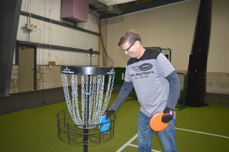 Jordan Beck | Daily Press After a round of putting during the first meeting of the Noc Bay Flyers Disc Golf Club's Indoor Putting League, Robin Holmes retrieves his discs from a goal basket set up at the Hannahville Ice and Turf Complex Monday.