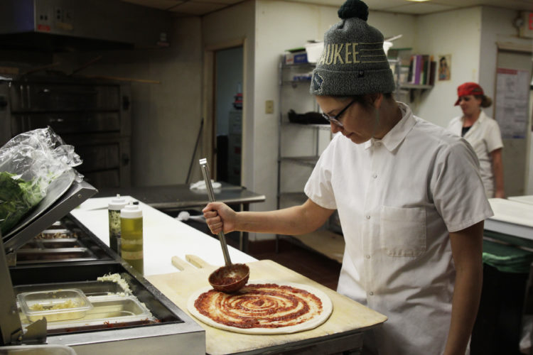 AP Photo/Carrie Antlfinger In this Jan. 9, 2017, photo, Andrea Ledesma spreads sauce on pizza dough at Classic Slice restaurant in Milwaukee. The 28-year-old has a four-year degree and quit a higher paying job because it made her miserable. Ledesma thought she would be making more at this point in her life and she's not alone.
