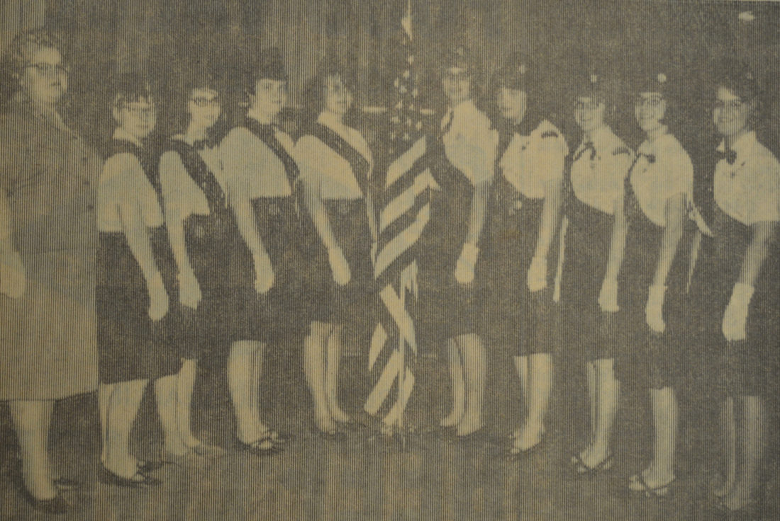"Daily Press photo Cadettes from Troops 2 and 4 of Escanaba were received into Senior Girl Scout Troop 24 in a traditional capping ceremony at the V.F.W Hall in this 1966 photograph. The program included an opening flag ceremony and a ""dramatic skit."" Pictured from left are: Mrs. Clifford Mineau, Barbara Schmit, Laurel Weiland, Joan McDonnell, Gladys Williams, Maureen Richards, Ann Schmidt, Diane Rose, Pat McMonagle, and Katie Prininski."