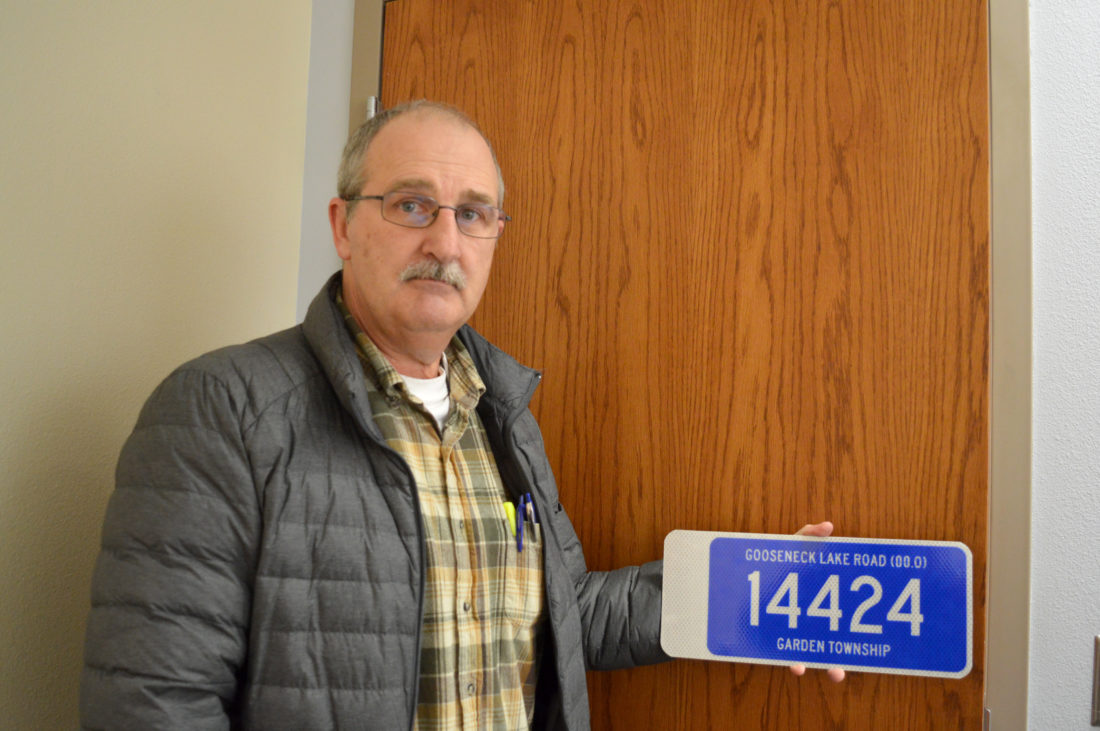 Jordan Beck | Daily Press Delta County Emergency Management Coordinator Bob Berbohm holds a mock-up fire number sign Tuesday. If project funding is approved by the Delta County Board of Commissioners, similar signs could be implemented in Delta County townships.