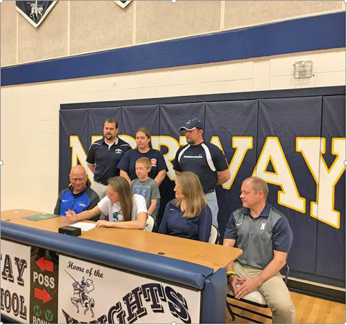 Courtesy photo Norway's Jordan Kraemer signed a national letter of intent last week to attend Bay College and play basketball for the Norse. Bay coach Rae Drake Jr., seated far left, watches the signing next to Kraemer, who was the U.P. Class ABC Player of the Year.