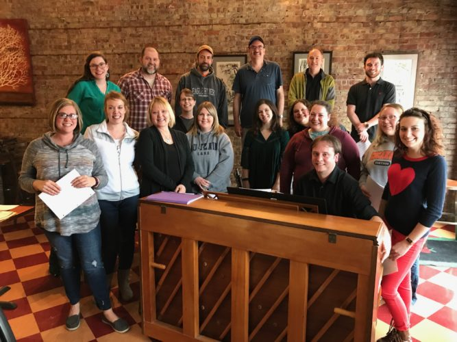 Courtesy photo Members of The Esky Pops are working on song selections for the new group's first rehearsal on May 21 under the direction of Travis Dubord (seated at piano). Choir members (back row from left to right), Elise Low-Edwardson, Jamie Peterson, Jeff Woerpel, Jim Powell, Kris Pfotenhauer, Brennan Richardson, (front row from left to right), Amy Dier, Samantha White, Karen Beveridge, Beth Peterson, Mollie Breitzman, Erica Mead, Cindy Belanger, Macy Neumeier, Bri Belanger, Autumn Fournier.