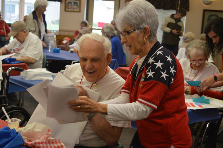 Haley Gustafson | Daily Press  Bishop Noa Home resident and World War II veteran Frank Demars listens to letters written to him from Honor Flight Volunteer Ada Knauf Tuesday during the mail call portion  of Mission XII.V of the Upper Peninsula Honor Flight at Bishop Noa Home in Escanaba.