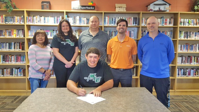 Courtesy photo Escanaba's Johnny Kositzky (seated) recently signed a national letter of intent to attend Wisconsin Lutheran College and play golf.  Attending the signing and standing from left: grandmother Naty Steele, mother Lisa Kositzky, father John Kositzky, assistant golf coach Jake Berlinski and head coach Brian Robinette.