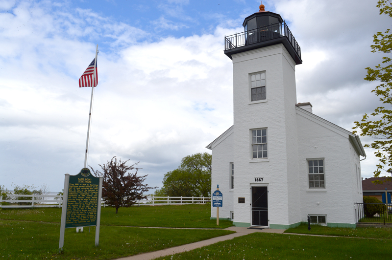Haley Gustafson   Daily Press Above, the Sand Point Lighthouse in Escanaba sits under a cloudy sky Tuesday afternoon. The lighthouse will be honored on July 3 at 1:30 p.m. by the Delta County Historical Society (DCHS) to commemorate its 150th anniversary. The lighthouse began servicing mariners on Little Bay de Noc on May 13, 1868 and continued to do so until 1939.