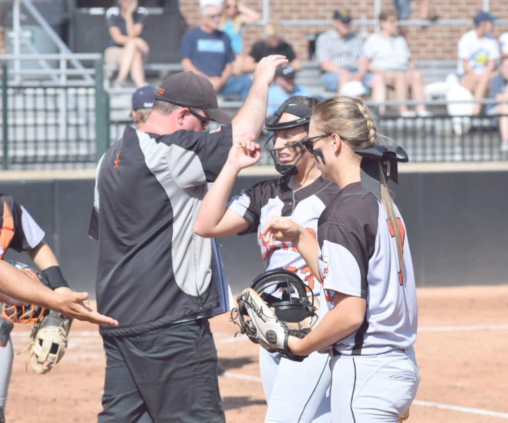 Mike Mattson | Daily Press Escanaba pitcher Katie Ross, center, gets congratulated by assistant coach Andy Fields, left, and second baseman Claire McInerney after the second inning.