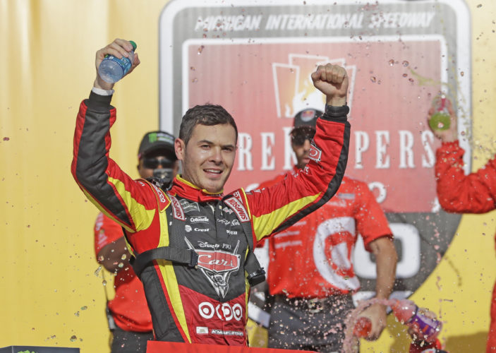 AP photo Kyle Larson celebrates after exiting his car after winning a NASCAR Sprint Cup series auto race, Sunday in Brooklyn, Mich.