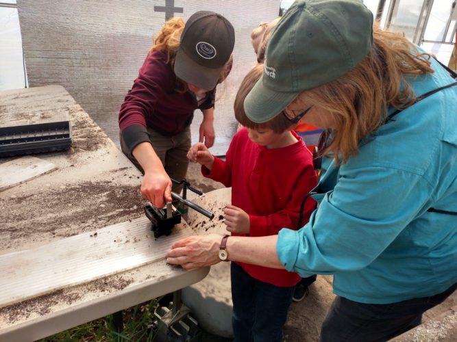 "Courtesy photo Allison Stewara, Assistant Production Manager at the Nort Farm (left) and Cindy Bender, Webster Parent Involvement Coordinator assist Cooper Lanaville  creating a ""soil block"" for planting seeds."