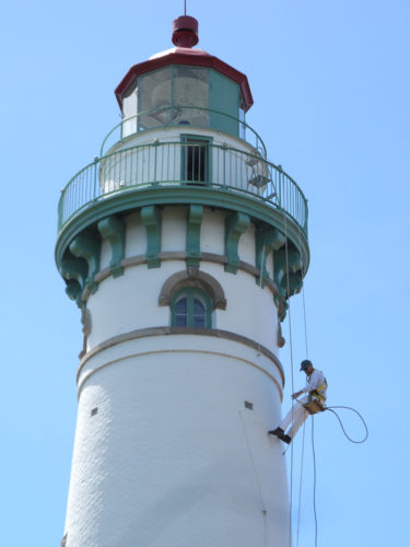 Courtesy photo Carl Behrend of Old Country Decorating and Painting of Munising, hangs from the top of the Seul Choix Pointe Lighthouse in a bosun chair while painting the structure.
