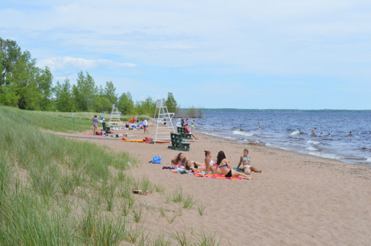 Haley Gustafson | Daily Press Beach goers enjoy warm sunshine and the water last week at the Escanaba Public Beach. Today marks the official first day of summer and going to the beach is just one of the many activities residents and visitors alike can enjoy throughout the summer months in the area. Temperatures are expected to reach 70 degrees today, with partly sunny skies.