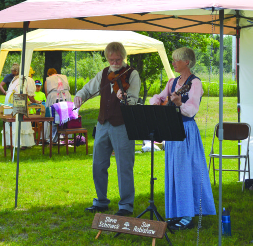 Daily Press file photo Pictured at right, folk musicians Steve Schmeck and Sue Robishaw perform during the 2016 Pioneer Day in Manistique. The annual event features artisans, performers, food, and a look into the area's history.