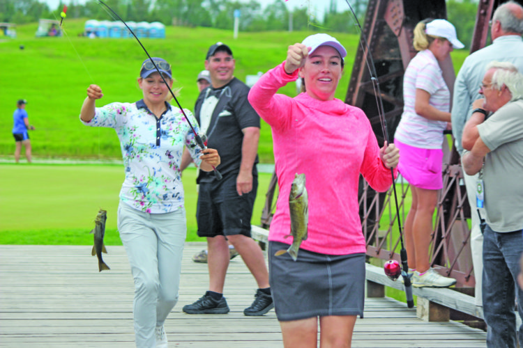 Dennis Grall photo Marita Engzelius, left, of Oslo, Norway and Karlin Beck of Montgomery, Ala. run onto the island green bridge at Sweetgrass Golf Club with fish they caught Thursday in the Bassmaster Fish tournament as part of the Island Resort Championship at Sweetgrass. The Symetra Tour golf tourney began this morning, with the final round Sunday.