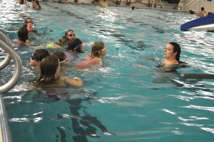 Haley Gustafson | Daily Press  Northern Lights YMCA lifeguard Kayla Wiltzius instructs swimmers on how to tread water during the World's Largest Swiming Lesson (WLSL) event held at the YMCA in Escanaba Thursday.